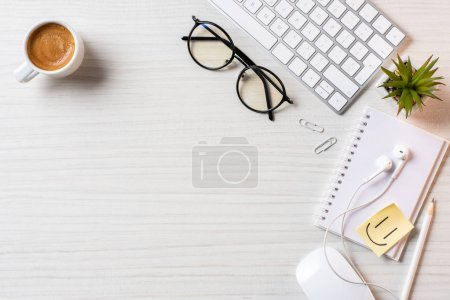 Photo pour Vue surélevée des lunettes, tasse à café, symbole de sourire et écouteurs à la table au bureau - image libre de droit