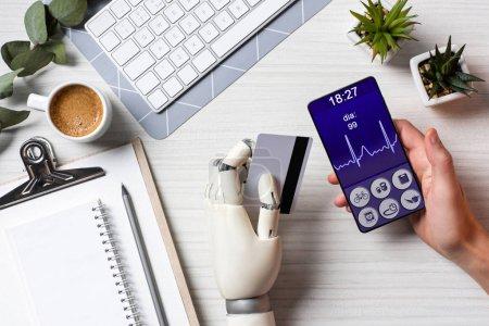 Photo pour Vue partielle de l'homme d'affaires main cyborg détenant la carte de crédit et à l'aide de smartphone avec l'application médicale sur l'écran à table avec une tasse de café au bureau - image libre de droit