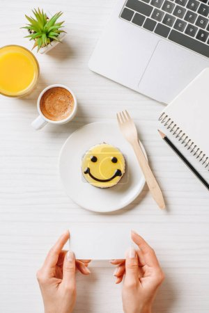 Photo for Cropped image of businesswoman holding empty visit card at table with orange juice, coffee cup and cake with symbol of smile in office - Royalty Free Image