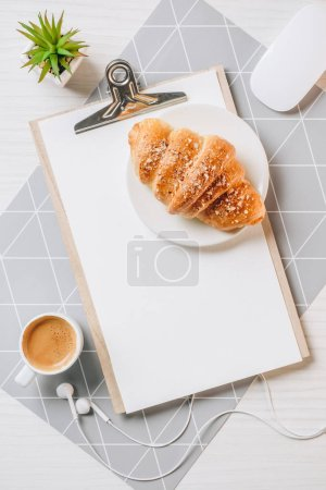 flat lay with croissant, coffee cup, computer mouse and blank clipboard at table in office