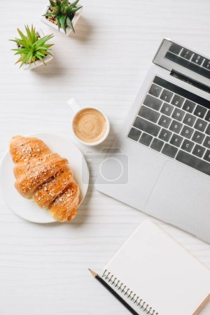 top view of workplace with laptop, empty textbook, croissant and coffee cup in office