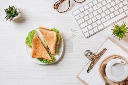 Photo pour Vue de dessus de tasse à café jetable, sandwich, clavier d'ordinateur et lunettes à la table dans le bureau - image libre de droit