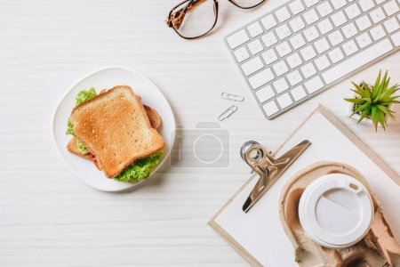 elevated view of paper coffee cup, sandwich and computer keyboard at table in office