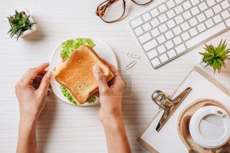 abgeschnittenes Bild einer Geschäftsfrau beim Mittagessen mit Sandwich und Kaffee in Pappbecher am Tisch mit Computertastatur im Büro
