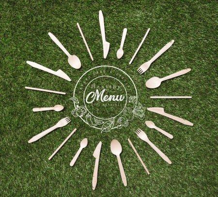 vue de dessus des cuillères en bois avec fourchettes et couteaux en forme de soleil couché sur l'herbe, inscription menu