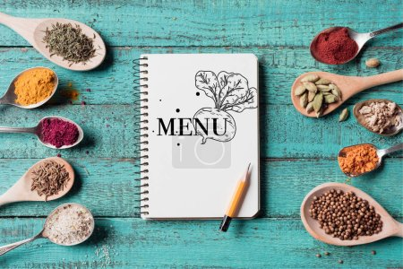 top view of menu inscription in notebook with pencil and spoons with various spices on turquoise wooden surface
