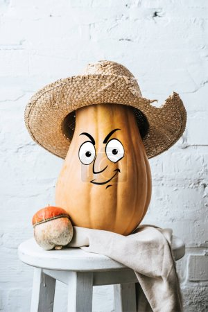 close up view of ripe pumpkins with drawn smiley facial expression and straw hat on wooden stool and white brick wall backdrop