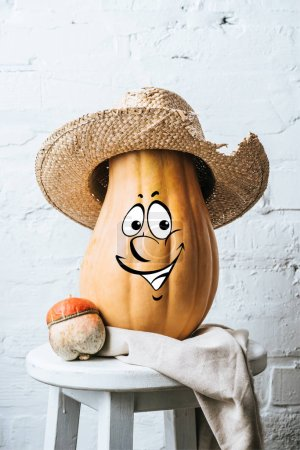 close up view of ripe pumpkins with drawn smiley facial expression and straw hat on wooden surface and white brick wall backdrop