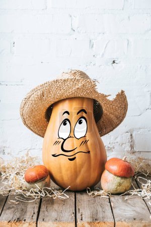 close up view of ripe pumpkins with drawn bewildered facial expression and straw hat on wooden surface and white brick wall backdrop