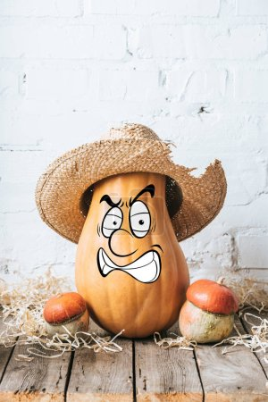close up view of ripe pumpkins with drawn angry facial expression and straw hat on wooden surface and white brick wall backdrop