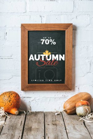 close up view of raw pumpkins on wooden tabletop and chalkboard with autumn sale inscription hanging on white brick wall