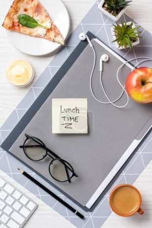 top view of sticky note with inscription lunch time, eyeglasses, earphones, pizza an apple on table