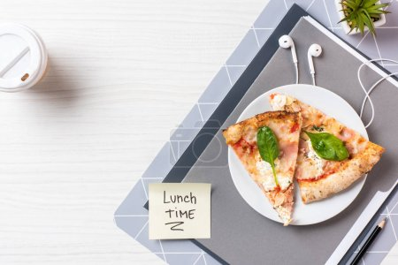 top view of sticky note with inscription lunch time, earphones and pizza on table