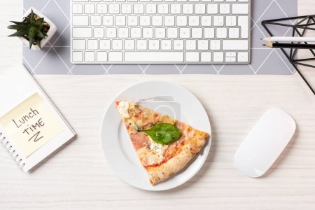 top view of pizza on plate, note with lunch time inscription, computer mouse and keyboard at workplace
