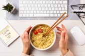 cropped shot of person holding bowl with noodles and chopsticks at workplace