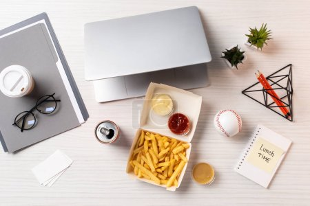 top view of french fries, soda can, laptop and office supplies at workplace