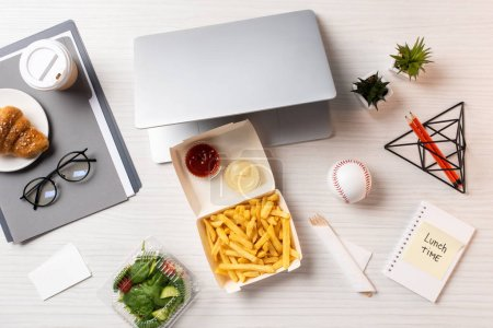 top view of french fries, laptop, vegetable salad and office supplies at workplace
