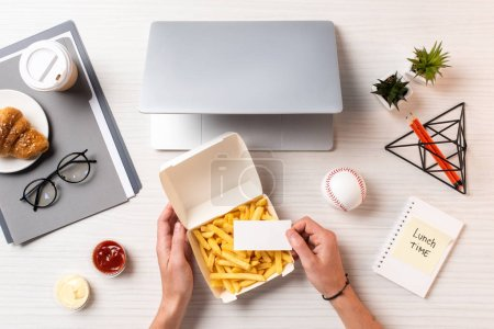 cropped shot of person holding blank card above container with french fries at workplace
