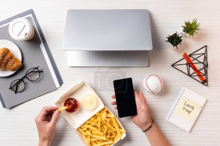 cropped shot of person eating french fries with ketchup and using smartphone with blank screen at workplace
