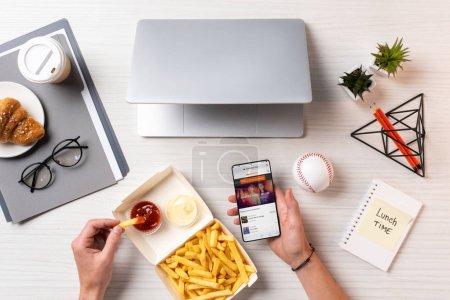 Photo for Cropped shot of person eating french fries with ketchup and using smartphone with soundcloud app at workplace - Royalty Free Image