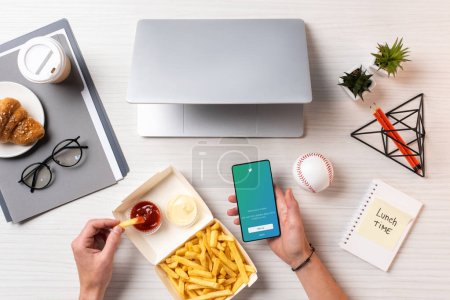 Photo for Cropped shot of person eating french fries with ketchup and using smartphone with twitter application at workplace - Royalty Free Image