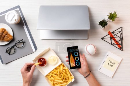 Photo for Cropped shot of person eating french fries with ketchup and using smartphone with business charts at workplace - Royalty Free Image