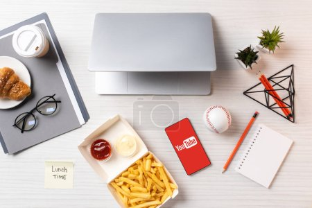 Photo for Top view of french fries, sticky note with inscription lunch time, laptop and smartphone with youtube application at workplace - Royalty Free Image