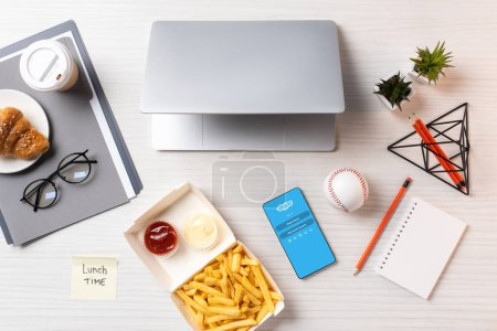 top view of french fries, sticky note with inscription lunch time, laptop and smartphone with skype application at workplace