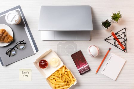 top view of french fries, sticky note with inscription lunch time, laptop and smartphone with trading courses charts at workplace