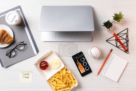 top view of french fries, sticky note with inscription lunch time, laptop and smartphone with charts at workplace