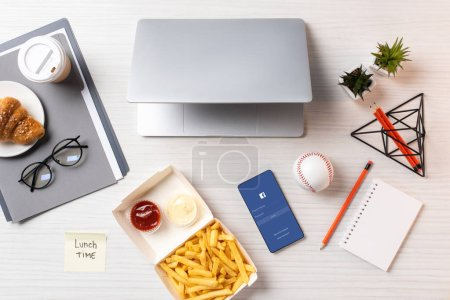 Photo for Top view of french fries, sticky note with inscription lunch time, laptop and smartphone with facebook application at workplace - Royalty Free Image