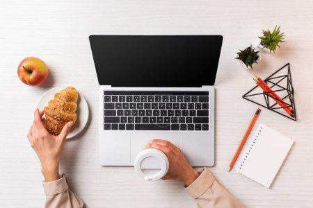 Foto de Foto recortada de empresaria sosteniendo la taza desechable de café y un croissant al utilizar portátil con pantalla en blanco - Imagen libre de derechos