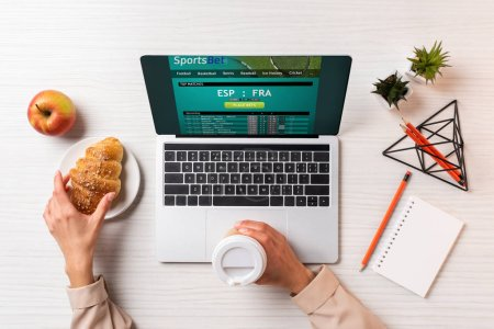 cropped shot of businesswoman holding disposable coffee cup and croissant while using laptop with sports bet website