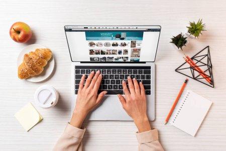 plan recadré de femme d'affaires à l'aide d'un ordinateur portable avec site amazone à table avec café, pomme et croissant