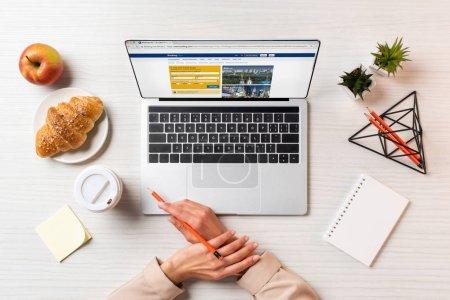 Photo pour Photo recadrée de mains féminines, ordinateur portable avec le site Web de réservations et déjeuner sur la table au bureau - image libre de droit