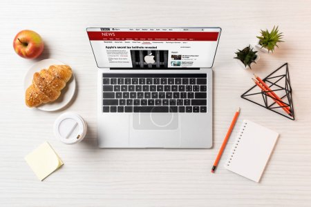 top view of laptop with bbc news website, croissant and coffee to go on office table