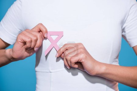 partial view of woman holding breast cancer awareness pink ribbon on blue background