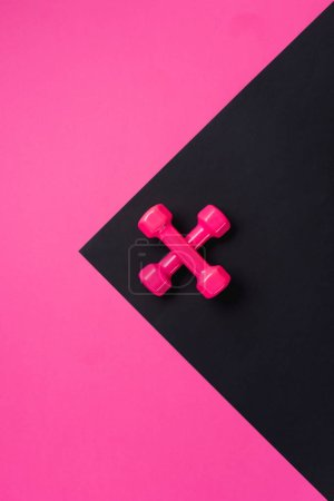 top view of two crossed dumbbells on black and pink background with copy space