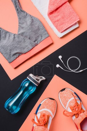 Photo for Top view of sneakers, dumbbells, sport bottle, towel, sportswear and headphones on black background - Royalty Free Image