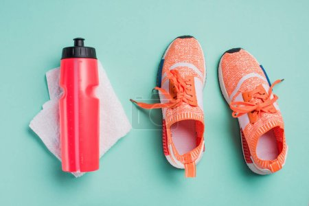 Top view of sneakers, sport bottle and towel on turquoise background
