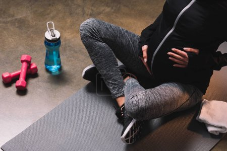 Cropped view of pregnant sporty woman sitting on the sportive mat and sport bottle beside