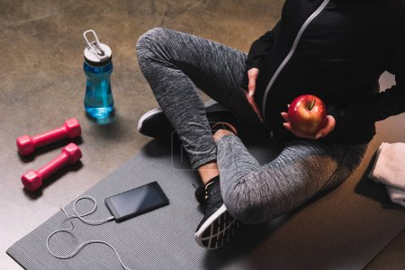 Cropped view of pregnant sporty woman sitting on the sportive mat with apple in hands