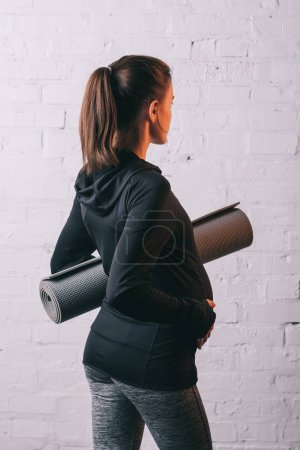 Back view of athletic pragnant woman with sports mat