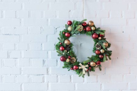 Foto de Guirnalda de Navidad decorado con bolas y lazo en el fondo de pared de ladrillo blanco - Imagen libre de derechos