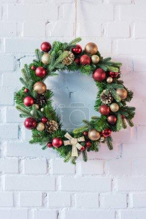 Photo pour Guirlande de Noël accroché sur le mur de briques blanches - image libre de droit