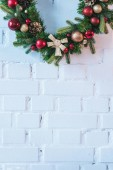 close up of Christmas wreath on the background of white brick wall