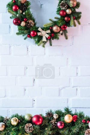 Foto de Corona de Navidad con bolas de Navidad en el fondo de pared de ladrillo blanco - Imagen libre de derechos