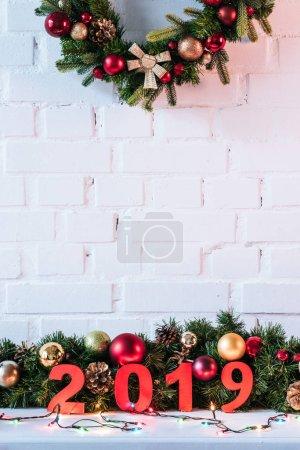 Foto de Guirnalda de la Navidad y el año 2019 se cantan en el fondo de pared de ladrillo blanco - Imagen libre de derechos
