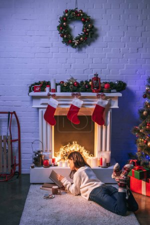Photo for Adorable woman reading near christmas decorated fireplace and Christmas tree - Royalty Free Image