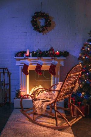 Foto de Chimenea con adornos de Navidad cerca del árbol de Navidad y mecedora de madera - Imagen libre de derechos